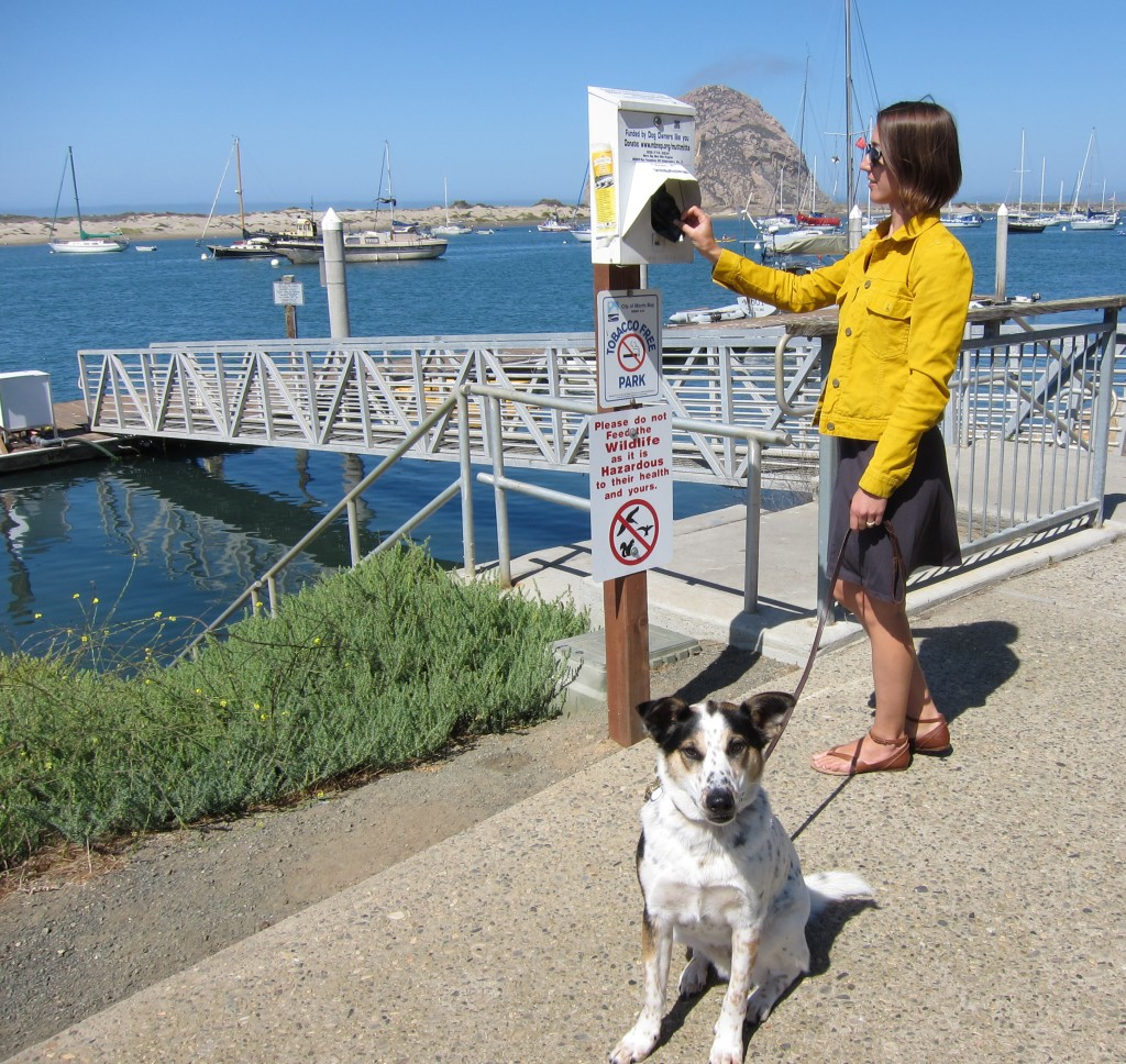 Morro Bay National Estuary Program's Assistant Director, Lexie Bell, and her dog BB visit the Mutt Mitts dispenser in Tidelands Park.