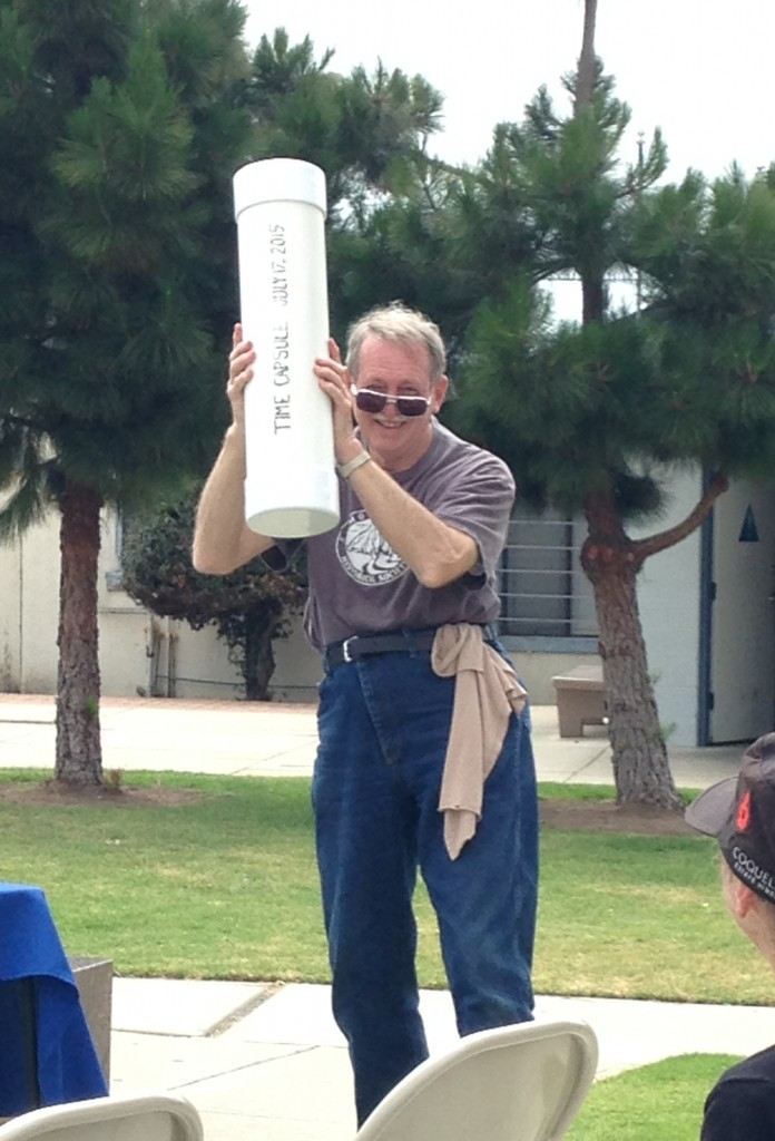 Roger Castle holds the time capsule aloft.