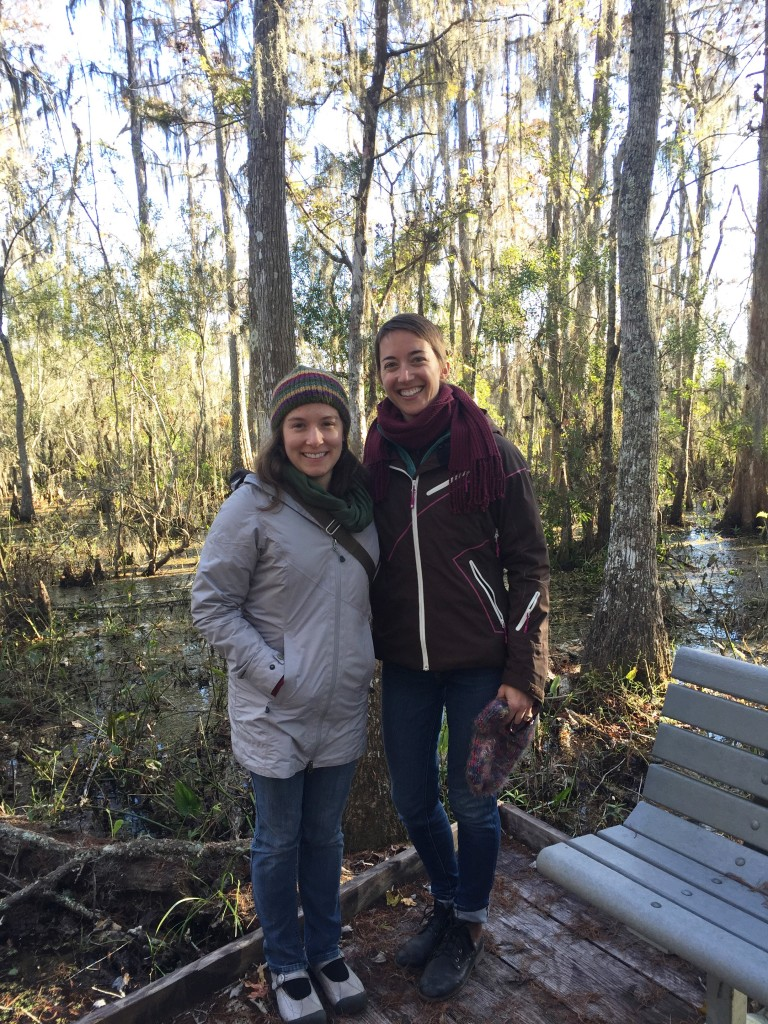 Communications and Outreach Coordinator Rachel Pass (left) and Executive Director Lexie Bell (right) stand in front of a bald cypress swamp in Jean Lafitte National Park outside of New Orleans, Louisiana.