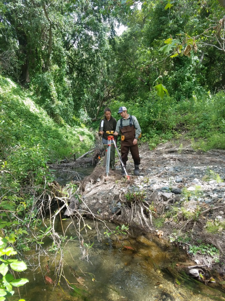 Evan, our Field Technician, shows a volunteer how to use a device called an auto level to measure the slope of the stream. An auto level is essentially a telescope that allows us to measure the elevations of our transects (the set areas where we are collecting data) from a fixed location along the stream.