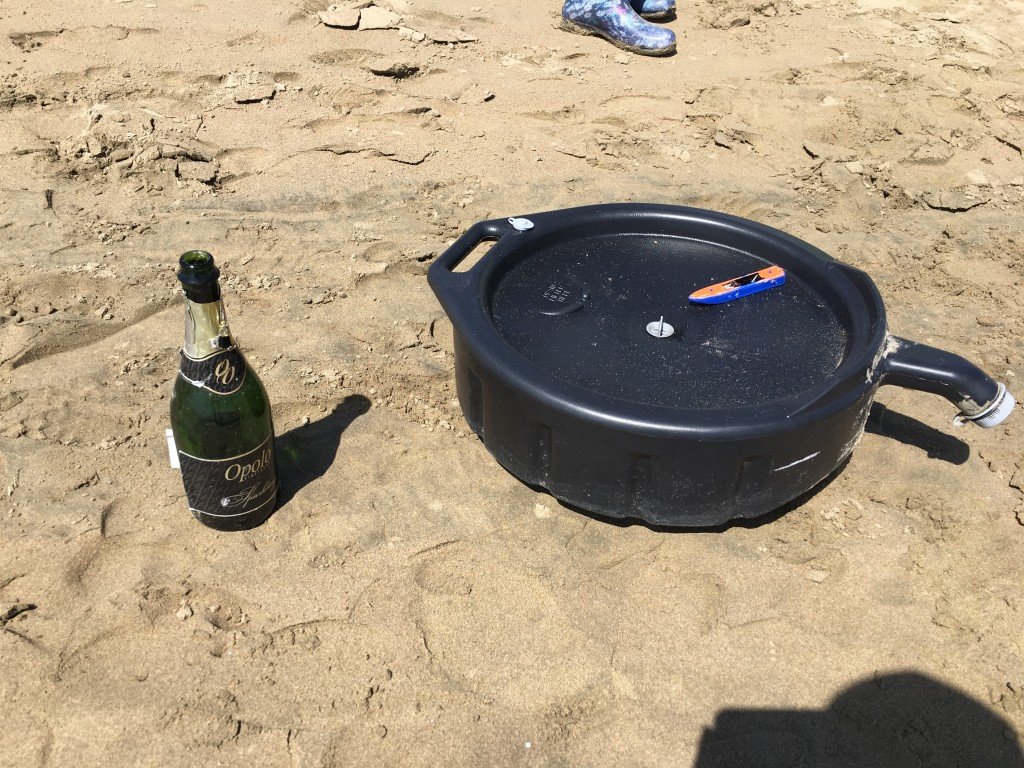 A few of our strange items, including a half-full bottle of champagne, a used oil pan, and a toy boat.