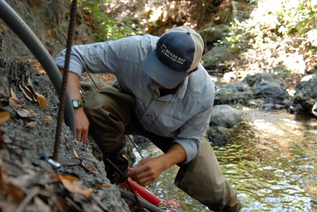 Shane utilizes the stream bank to anchor the end of the pressure transducer.