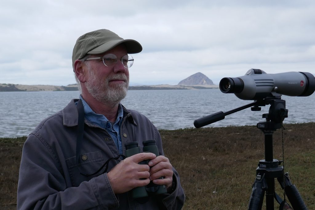 John Roser stands near the Morro Bay estuary, scope and binoculars at the ready.