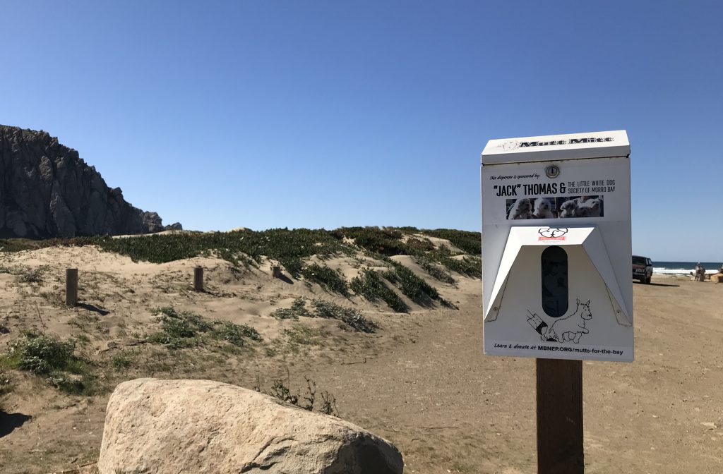 """We show our thanks for each sponsor with a custom sticker on their dispenser. This dispenser at the Morro Creek Bridge is sponsored by """"Jack"""" Thomas and the Little White Dog Society of Morro Bay. They may be our fluffiest group of sponsors to date!"""