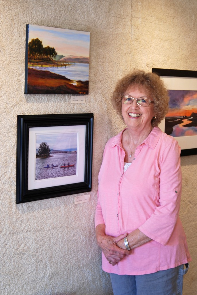 Sylvia Arnold-Hill poses with her acrylic painting of the back bay (top left on wall)