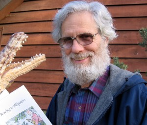 """George Asdel poses with his chapbook, """"Reading to Alligators."""""""