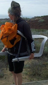A woman with an orange backpack carries a plastic chair and looks out toward the sand dunes.