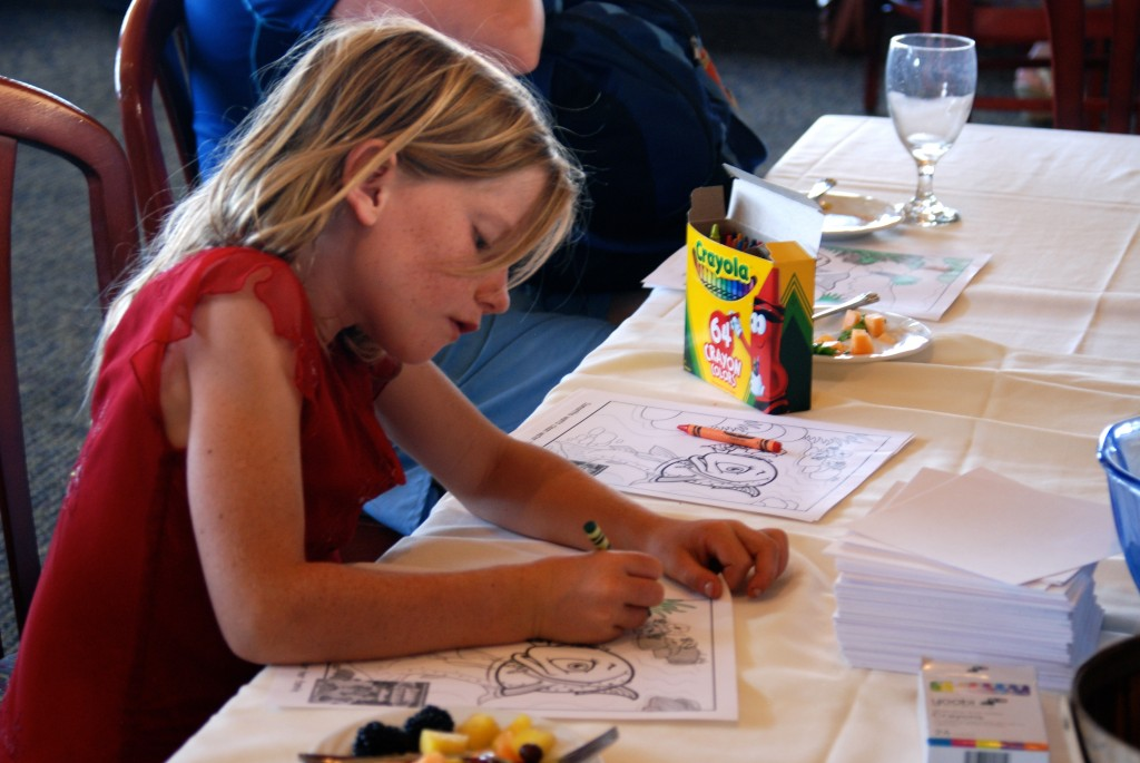 A girl colors a picture of Sammy the Steelhead Trout during the party.