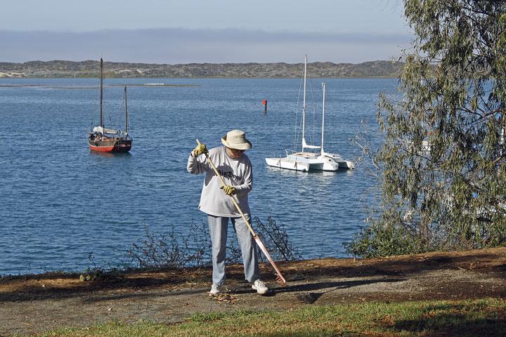 Doreen rakes the path along the water's edge. Photograph courtesy of Ruth Ann Angus.