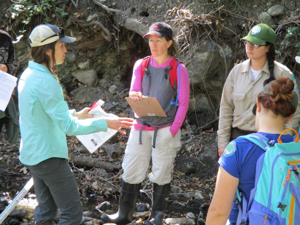 Monitoring Coordinator Karissa explains to volunteers how to collect habitat data such as water depth and creek bottom characteristics.