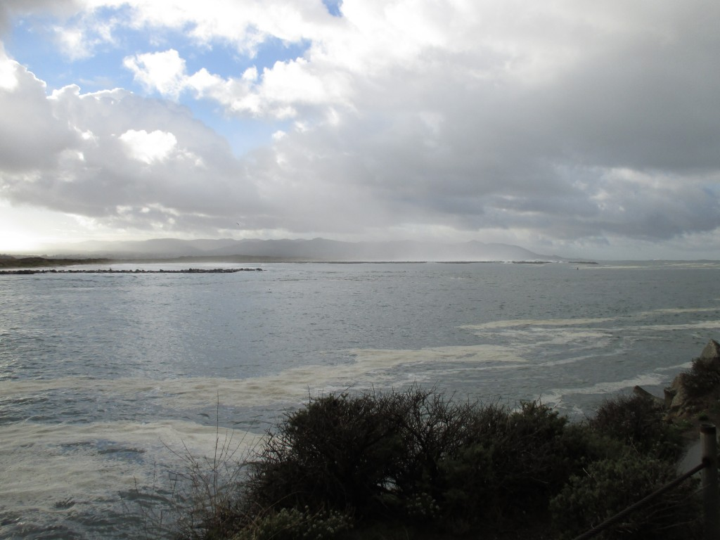 Clouds roll in over the harbor mouth on a stormy morning.