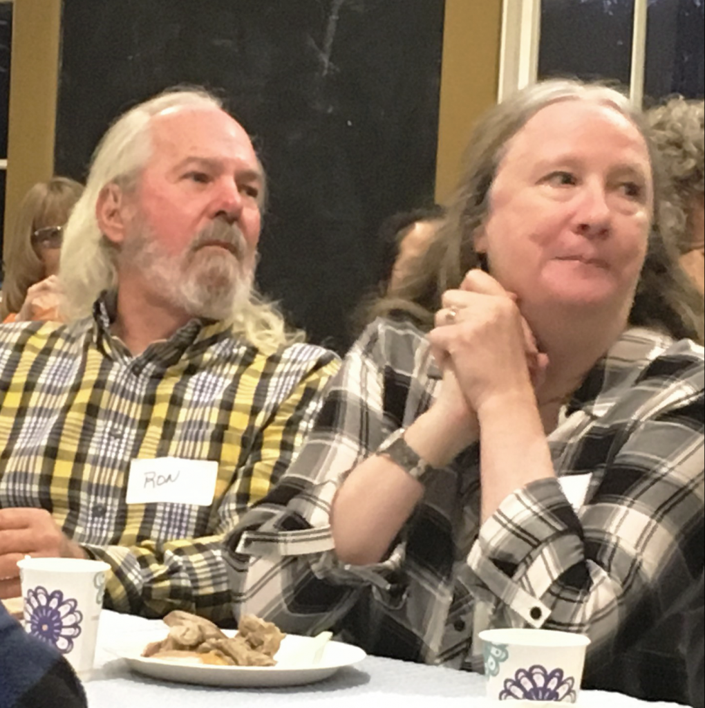 Ron Ruppert, on left, listens to Executive Director Lexie Bell welcome volunteers to our appreciation event.