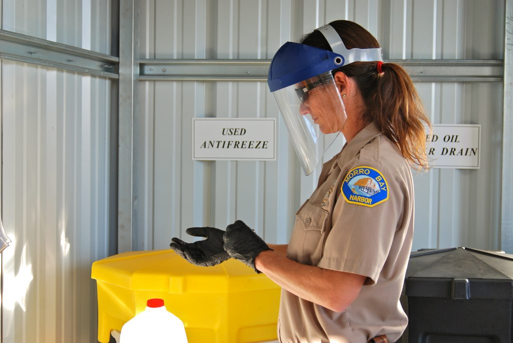 Becka Kelly, Harbor Department Supervisor, dons protective gear before pouring some oil into the drum to be recycled.