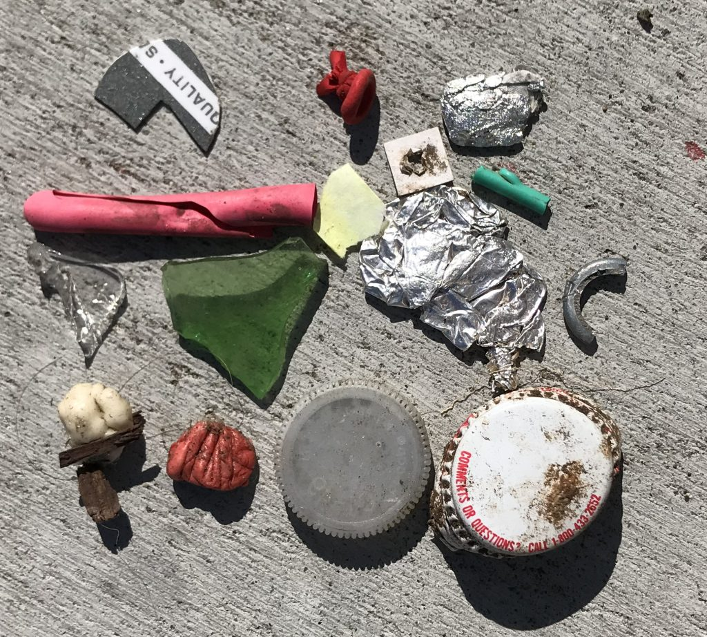 This photograph shows a collection of tiny trash pieces. They may be small, but removing them from the environment can have a big positive impact.