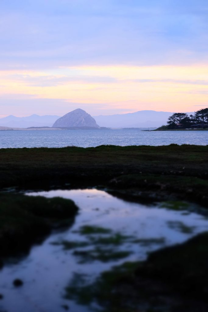 Sunset photograph of Morro Bay estuary with Morro Rock in the background.