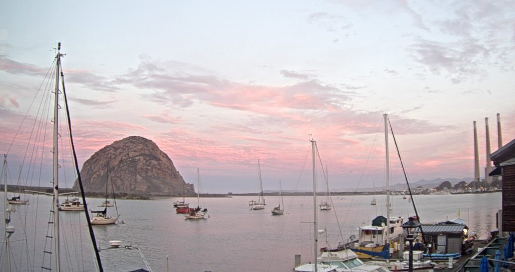 A pink and purple sunrise behind Morro Rock
