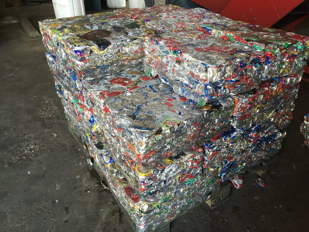 Aluminum cans are compacted and bound together for transport.