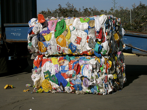 Plastic waste is compacted and bound together for transport.