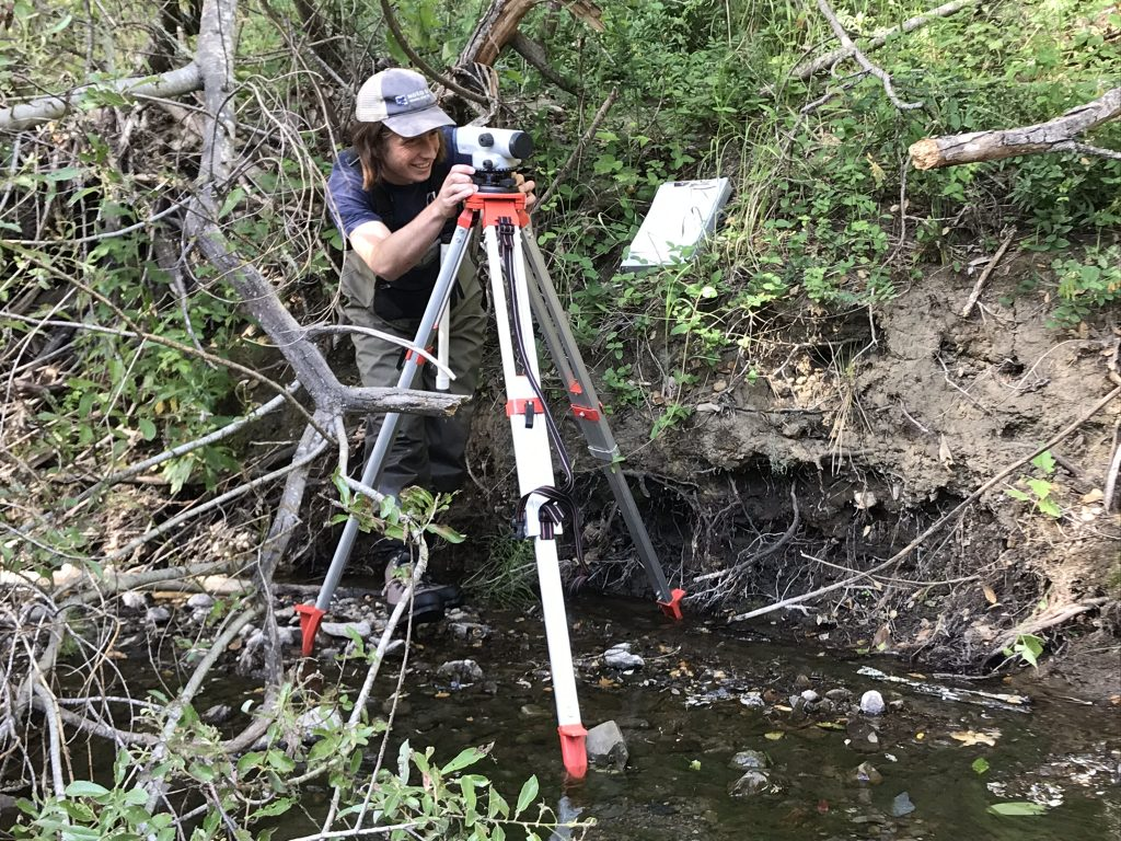 Tyler, Field Technician, surveys stream height.