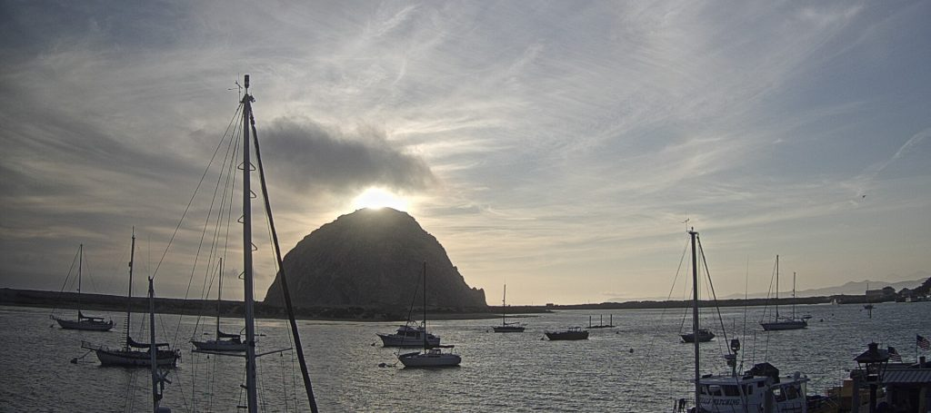 Morro Rock and clouds illuminated from behind.