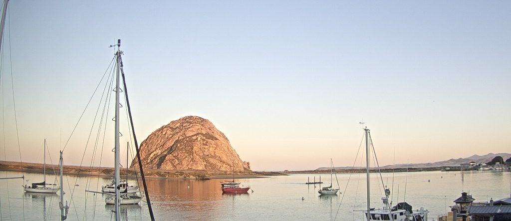 Golden morning light glows behind Morro Rock.