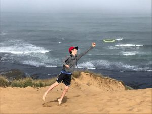 Eli Hague, poetry contest winner leaps to catch a frisbee near the ocean.