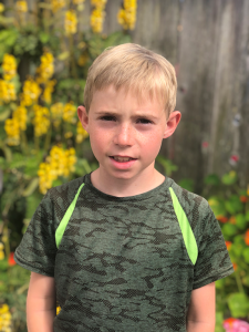 Seamus Wolf looks at the camera. he has brown hair, wears a grey shirt with green diagonal stripes at the shoulders, and stands in front of yellow flowers, green foliage, and a brown fence.
