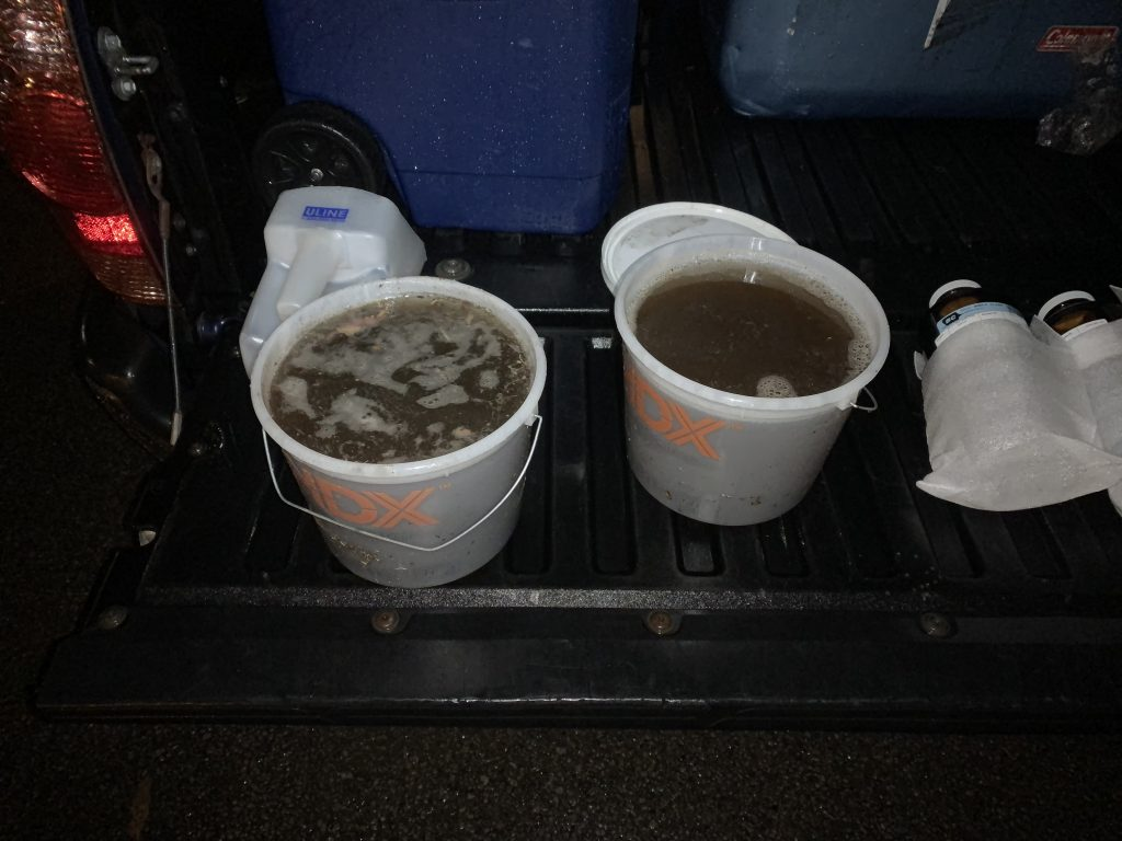 The stormwater samples appear very dark in color due to the high levels of sediment they contain. The technicians first collected runoff in the large containers on the left and then poured it into the smaller sample jars pictured on the right. After collection, the samples were stored on ice and then sent to a lab for analysis.