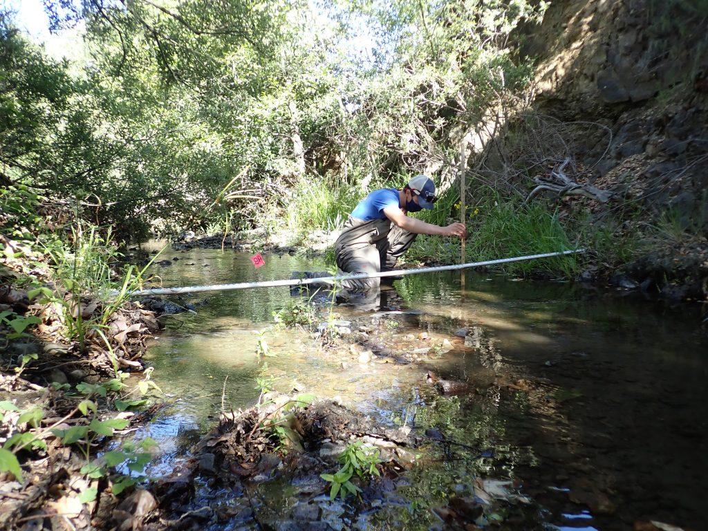 An Estuary Program staff member takes water depth measurements.