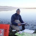 Bret Fickes, Monitoring Projects Manager, Morro Bay National Estuary Program kneels in an eelgrass bed while monitoring its health.